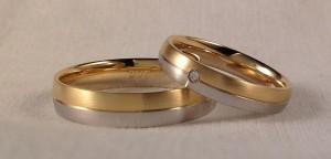 Ella: modelo 320 de 4 mm de ancho, una mitad va en oro amarillo y la otra en oro blanco, las dos satinadas, con el acabado premiun, lleva un diamante justo en el centro de 0,025 kt, El: el mismo modelo, el 320 pero en 5 mm de ancho y acabado confort. En este caso las dos alianzas son del mismo modelo, buscando la diferencia en el ancho, ya que gastan dos números muy distintos, la de él es de 5 mm con el acabado confort y la de ella es en 4 mm y acabado premium, puestas cada una en su mano parecerán iguales, solamente con la diferencia del brillante central, que destaca mas gracias al acabado satinado