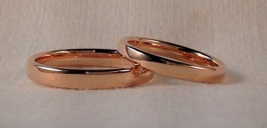 Ella: alianza oval en oro rojo de 3 mm, acabado brillo, El: La misma pero en 3,5 mm. Estas dos alianzas a pesar de parecer clásicas, han decidido darle un toque mas moderno con el color del oro y con la forma oval, una forma que hace que sean muy cómodas y muy resistentes. También las han encargado en dos anchos diferentes ella de 3 mm y el un poco mas ancha, 3,5