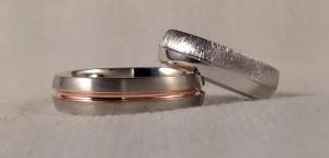 Esta pareja ha decidido elegir dos alianzas diferentes, aunque con algun punto de unión (la forma y el color). Ambas son en oro blanco, sección almendrada y acabado Premium de 5 mm., el ha elegido un acabado satinado, con un toque de oro rojo en el centro y ella ha combinado el brillo, con el mate diamantado. Ella: modelo 127 de 5mm en oro blanco, brillo/diamantado, premium;  El: modelo 334 de 5 mm en oro blanco y rojo, satinado, premium