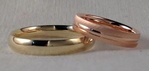 Dos alianzas diferentes, pero que se complementan muy bien, la de ella es una surco en oro rojo, lleva el centro en brillo, un poco mas bajo que los laterales acabados en un mate grueso, que le da un contraste muy interesante. El se decidió por una almendrada, muy cómoda, al ser curva por el interior y en oro amarillo brillo.  Ella: mod. Surco, 4 mm, oro rojo, brillo y mate grueso;  El: Almendrada, 4mm, oro amarillo brillo