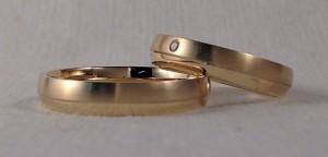 Estas dos alianzas son del mismo modelo, el 127, tiene un pequeño escalón asimétrico, para poder dar dos acabados diferentes, en este caso pulido/satinado, las dos son de 4 mm y acabado confort, ella le ha puesto un diamante de 0,015 kt, en la parte satinada.  Ella: Mod. 127, 4 mm, oro amarillo, pulido/satinado, confort, diamante de 0,015 kt;  El: El mismo modelo y acabado, pero sin diamante