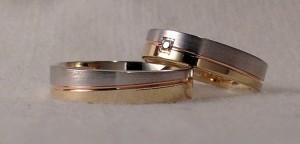 Esta pareja, escogió el modelo 6451. Es una alianza muy curiosa, ya que al llevar la raya central en diagonal, hace que según la posición, se vea mas ancho el oro blanco mate y en otra, el oro amarillo brillo, además aun la personalizaron mas al pedir que esa raya fuera en oro rojo y ella le añadió un diamante central de 0,02 kt. Ella: modelo 6454, 4,5 mm, oro tricolor, pulido/satinado, confort 1,3, diamante 0,02 kt; El: El mismo modelo sin diamante