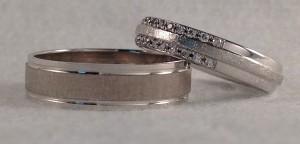 En este caso, se decidieron por dos alianzas distintas, pero que sin embargo, buscan tener detalles comunes. Ambas están hechas en oro blanco, con el centro mate y los laterales pulidos y ella además le añadió dos filas de diamantes a media alianza, lo que hace que sea muy original. Ella: modelo 14-NJ-116, 4 mm, oro blanco, pulido/mate, 22 diamantes 0,10 kt El:    modelo 6420, 5x1 mm, oro blanco, pulido/rayado