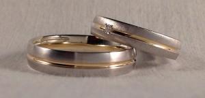 Estas dos alianzas son muy similares, aunque de fabricantes diferentes, ya que buscaban que tuvieran algo en común. En este caso las dos llevan un canal en el centro en oro amarillo brillo y el oro blanco es satinado en el caso de la de él y rayado en la de ella, que además le añadió un diamante de 0,02 kt para realzarla aun mas.  Ella.- modelo 6644, 4,5 mm, oro blanco rayado, amarillo brillo, confort 1,5, diamante 0,02 kt;  El.- modelo 334, 5 mm, oro blanco satinado, amarillo brillo, premium