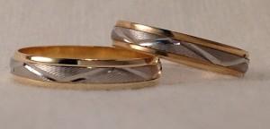 Esta pareja escogió el modelo 375207, que lleva una una onda central sobre un fondo tallado en oro blanco, los laterales son en oro amarillo brillo, el ancho es de 4 mm  Ella y él: modelo 375207, en oro bicolor, tallado/brillo, 4 mm
