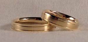 Estas alianzas son dos modelos prácticamente iguales, solo se diferencian en que la de él, es plana por el exterior y la de ella hace una forma mas redondeada, ambas tienen tres bandas, siendo la del centro mate satinada, para que destaque un poco mas. En este caso, aunque no es  lo habitual, la de ella es 1 mm mas ancha que la de él. Ella.- modelo 112, 5 mm, oro amarillo, pulido/satinado, premium El.-    modelo 117, 4 mm, oro amarillo, pulido/satinado, premium