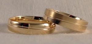 En este caso, también se decidieron por dos alianzas similares. Su característica mas destacada es la raya diagonal que cruza la alianza, lo que hace que según se gira se vea mas ancho el mate o el brillo. El se decidió por la forma de media caña y toda en brillo y ella la escogió plana y combinando el mate satinado y el brillo, ambas de 4,5 mm de ancho.  Ella.- modelo 6451, 4,5 mm, oro amarillo, pulido/satinado, confort 1,5;  El.- modelo 6427, 4,5 mm, oro amarillo, pulido, confort 1,3