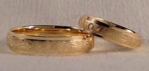 El modelo 130, se caracteriza por tener tres bandas, siendo la del centro mas ancha y mas alta, en este caso, le dieron un acabado diamantado, lo que hace que resalte mas y que sea mas resistente al uso cotidiano. Ambos eligieron el oro amarillo y el acabado confort, pero en anchos diferentes, él escogió la de 5 mm y ella la de 4 mm, además le añadió un diamante de 0,015 ct.  Ella.- modelo 130, 4 mm, oro amarillo pulido/diamantado, confort, diamante 0,015 ct;  El.- modelo 130, 5 mm, oro amarillo pulido/diamantado, confort