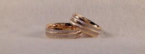 El modelo Bsatin, es muy curioso, ya que lleva uno o dos canales curvos por el centro, que cambian el reflejo al ir diamantados, además al ser cóncavos, quedan mas protegidos del desgaste diario. Esta pareja las escogió iguales, en dos colores y en 6 mm de ancho, por eso llevan dos canales en vez de uno.  Ella y él.- modelo Bsatin, 6 mm., oro amarillo/blanco, brillo/diamantado