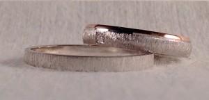 En este caso escogieron distintos modelos, aunque buscando características comunes como el acabado mate rayado en el oro blanco. El se decidió por el modelo 6602, plana y con solo 2,5 mm de ancho por 1 de alto, en oro blanco rayado. Ella eligió el modelo 6484, con una ligera curva exterior, un poco mas ancha de 3,5 mm por 1 de alto, la terminación del oro blanco también es rayado, pero el oro rojo lo dejo pulido y además le añadió un diamante de 0,015 ct montado en caja cuadrada.  Ella.- modelo 6484, 3,5x1 mm, oro blanco/rojo, rayado, pulido, diamante de 0,015 ct; El.- Modelo 6602, 2,5x1 mm, oro blanco rayado.