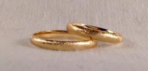 El modelo 101, es uno de los modelos clásicos de media caña, pero en este caso le dieron un acabado diamantado, en vez del habitual de brillo, que las hacen más resistentes a los rayones en el uso cotidiano. Ambos escogieron el ancho de 3 mm y el acabado confort.  Ella y el.- modelo 101, 3 mm, oro amarillo, diamantado, confort