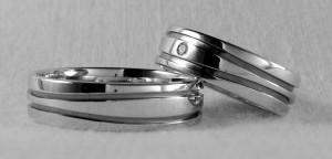 Un modelo muy original, es el Biarritz de la colección Marina. Se caracteriza por los dos surcos ondulados, que en este caso se han esmaltado en negro, para que haya más contraste con el oro blanco pulido de la alianza. Ambos escogieron el ancho de 6 mm y ella además le puso un diamante de 0,02ct.  Ella.- Biarritz, 6 mm, oro blanco, pulido, diamante 0,020 ct;  El.- mismo modelo y acabado pero sin diamante