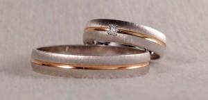 Esta pareja se decidió por el modelo 6644, se caracteriza por el canal central, que en este caso va en oro rojo brillo, así resalta mas sobre la base de la alianza que es el oro blanco rayado suave. Aunque es el mismo modelo, han elegido anchos y grosores diferentes, cada uno a su gusto y ella además le añadió un diamante de 0,020 ct en caja cuadrada.  Ella.- 6644, 4,5 mm x 1,3 confort, oro blanco rayado y rojo pulido, diamante 0,020ct;  El.- 6644, 4 mm x 1 plano, oro blanco rayado y rojo pulido