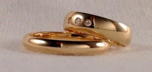 Estas dos alianzas son las clásicas de media caña, sin embargo cada uno la hizo a su gusto, ella eligió un ancho de 5x1 mm, con tres diamantes, siendo el central mas grande que los dos laterales. El, sin embargo prefirió que fuera más estrecha, de 3,5 mm, pero más alta, lo que la hace mas fuerte al desgaste.  Ella.- mod. 6303, 5x1 mm, oro amarillo, brillo, 2 diamantes de 0,015 y 1 de 0,020 ct;  El.- Mod. Mediacaña alta, 3,5 mm, oro amarillo, brillo