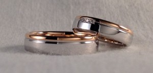 Estas dos alianzas son del 83102, tienen dos partes diferenciadas por un canal lateral. En esta ocasión, se decidieron por el oro blanco combinado con el rojo y el acabado pulido, ella eligió el ancho de 4,5x1,6 mm y además le añadió 3 diamantes en caja cuadrada de 0,021 ct., él escogió la misma sin diamantes y con el ancho de 5x1,6 mm  Ella.- mod. 83102, 4,5x1,6 mm, oro blanco/rojo, pulido, 3 diamantes 0,021 ct;  El.- mod. 83102, 5x1,6 mm, oro blanco/ rojo, pulido