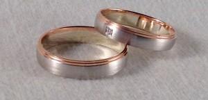 Esta pareja eligió el mismo modelo el 6621, que se caracteriza por tener 2 escalones en un lateral, ambas en oro blanco mate y rojo brillo, pero en anchos diferentes. Ella escogio 4x1 mm y un diamante de 0,015 ct y el de 4,5x1 sin diamante.  Ella: modelo 6621, 4x1 mm, oro blanco satinado, oro rojo pulido, diamante 0,015 ct.  El: mismo modelo y acabado, 4,5x1 mm