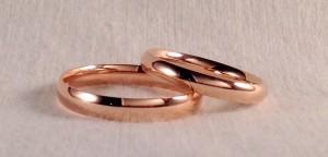 Dos alianzas del mismo modelo, que sin embargo tienen un ancho y un grosor diferente, la de ella es una almendrada de 3 mm, en oro rosa pulido y la de él es en 3,5 mm y en el acabado minimal, menos grueso. Han elegido esta opción, teniendo en cuenta el diferente uso que le van a dar.  Ella.- modelo almendrado, 3 mm, oro rojo, pulido;  El.- Modelo almendrado minimal, 3,5 mm, oro rojo, pulido