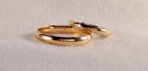 Dos alianzas del modelo de media caña, ambas en oro amarillo brillo, pero de anchos diferentes, él la escogió de 3,5 mm y ella de 2,5 y además le añadió un diamante de 0,015 ct para diferenciarla.  Ella.- modelo media caña, 2,5 mm, oro amarillo, brillo, diamante 0,015ct;  El.- mismo modelo y acabado en 3,5 mm