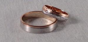 Aunque son modelos distintos, esta pareja utilizo los mismos colores de oro para sus alianzas. El escogió el modelo 6440, en color blanco y rojo mate, en un ancho de 5x1 mm. Ella se decidió por el 6428, con división en diagonal, el oro blanco y rojo en este caso lleva el acabado diamantado y le puso un diamante de 0,020 ct.  Ella: modelo 6428, 4,5x1 mm, oro blanco/rojo, diamantado, diamante 0,020 ct;  El: modelo 6440, 5x1 mm, oro blanco/rojo satinado