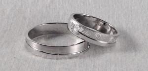 El modelo 6454, lo divide a la mitad una raya en diagonal, por lo que según la giremos, veremos mas un acabado u otro, en este caso él eligió el pulido/satinado y ella el pulido/diamantado, ambas son de 4,5x1 y ella le añadió un diamante en caja cuadrada de 0,020 ct.  Ella: modelo 6454, 4,5x1 mm, oro blanco, pulido/diamantado, diamante 0,020 ct;  El: modelo 6454, 4,5x1 mm, oro blanco, pulido/satinado