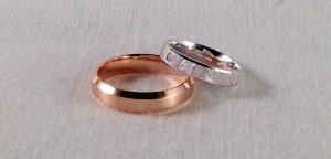 Estas dos alianzas, aunque parecen muy diferentes, es el mismo modelo pero con distintos acabados. El escogió el tono rosado, con un acabado mate suave en 5 mm premium y ella se decidió por una en oro blanco con un acabado diamantado, en 4x1,3 mm y además le añadió un diamante de 0,020 ct.  Ella: modelo 6393, 4x1,3 mm, oro blanco, diamantado, diamante 0,020 ct;  El: Modelo 125, 5 mm, oro rosa, mate satinado, premium
