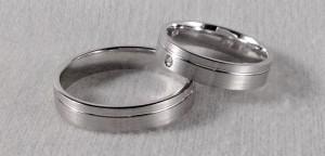 En esta ocasión, se decidieron por dos alianzas exactamente iguales, solamente que ella le añadió un diamante de 0,20 ct. desplazado del centro ya que la raya divisoria también está más cerca de un lateral. Ambas son de oro blanco satinado de 4,5x1,3 mm  Ella: modelo 6441, 4,5x1,3 mm, oro blanco, satinado, diamante 0,020 ct;  El: el mismo modelo y acabado, sin diamante