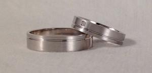 Estas dos alianzas son del mismo modelo, el 6440, la única diferencia es que la del chico es de 5x1 mm y la de ella es de 4x1,3 mm, para compensar las diferencias de mano, ya que una alianza ancha en una mano más grande parece igual que una más estrecha en una más pequeña. Además le añadió un diamante de 0,02 ct.  Ella.- modelo 6440, 4x1,3 mm, oro blanco, satinado, confort, diamante 0,02 ct;  El.- mismo modelo y acabado, 5x1 mm, plana